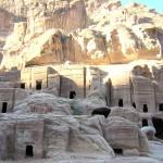 Rotsgraven in Petra. Mozes en Äaron komen rond 1200 v. Chr. in het huidige Jordanië aan. Mozes trekt vanuit Egypte over de Koningsweg door het huidige Zuid-Jordanië naar het Noorden (Num. 20: 14-21). Onderweg doet hij de antieke stad 'Petra' of 'rots' aan. Deze stad kun je nog steeds bezoeken. Allerlei zaken herinneren vandaag de dag nog aan Mozes. In een naburig dorp Wadi Musa of te wel 'Mozesvallei' kun je de bron zien die ontstond toen Mozes bij gebrek aan water tegen de rots sloeg (Num. 20:11). Het water gutst er nog steeds in een geul langs de weg. Je kijkt er op een hoge bergtop van 1350 m uit. Op de top staat een klein heiligdom met een witte koepel. Hier is Aäron -de broer van Mozes-  gestorven en begraven  (Num. 20:22-29). De bijbel spreekt van de berg Hor. De Arabieren spreken van de Jebel Harun of berg van Aäron. Aäron wordt net als Mozes bij de moslims geëerd als profeet. Direct na de dood van Aäron bij de berg Hor heeft het incident plaats van het morrende volk dat gestraft wordt met vuurspuwende en bijtende slangen. Mozes maakt daarop in opdracht van God een vuurspuwende bronzen slang en zet die op een houten paal. Het zijn beide godinnensymbolen. Ieder geneest (Num 21:9). Wanneer je de Aäronsberg via een duizelingwekkende pad beklimt, passeer je een gedenkteken in de vorm van een slang. Beneden in de vallei klampen Bedoeïnenvrouwen toeristen aan. Ze bieden Arabische godinnen aan én... de bronzen slang. Onder koning Salomo zal Zuid-Jordanië door de Israëlieten veroverd worden (1 Sam. 14:47-48).