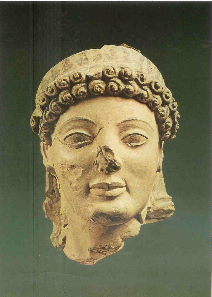 Athene. Zij draagt spiralende krullen en een met bloemen versierd diadeem. Laat-archaïsche periode 490 v. Chr. Thans in het museum te Olympia op de Peloponnesos.