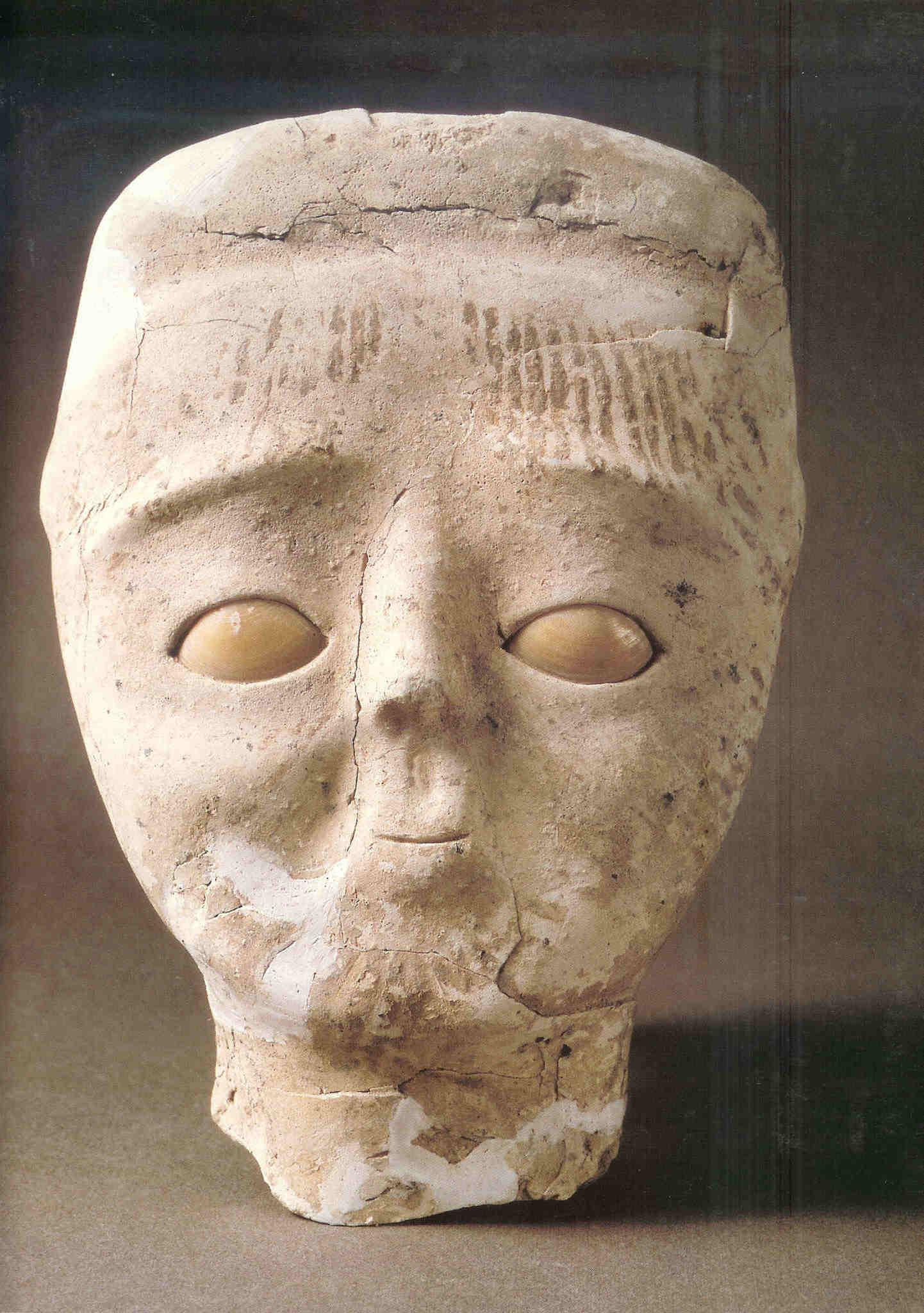 Beschilderd Gipsen Hoofd. Jericho, 7e millennium v. Chr. Met hoofdbedekking en lijnen op voorhoofd. Ogen zijn duidelijk aangegeven. Beeld wordt omschreven als 'gipsen hoofd van mensenfiguurtje' (Burenhult, De Eerste Mens, 232).