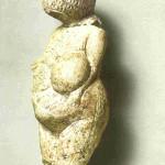 Vrouwe van Kostienki. Vanaf linkerzijde. Met gebogen hoofd en handen aan de zware buik. Kalksteen. 9.5 cm. 22.700 v. Chr. Thans in Museum voor Antropologie en Etnologie in St. Petersburg.