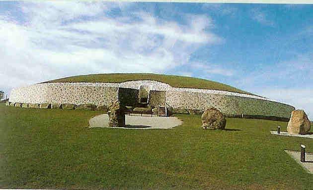 New Grange bij Dublin. Het heiligdom heeft een doorsnede van 79 bij 85 meter en is omgeven door 97 grote stenen of megalieten van ca drie meter hoogte die bijna alleen bewerkt en versierd zijn.