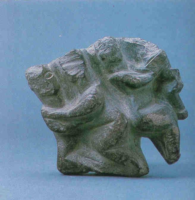 Het Heilige Viertal. Links omarmt een god godin, rechts drukt een godin haar kind tegen zich aan. Moeder en dochter die met de ruggen naar elkaar zijn toegekeerd, staan centraal. Hoogte 11.6 cm, breedte 11.3 cm. Catal Hüyük laag VI A, heiligdom 30. Tussen 6000 en 5500 v. Chr. Museum voor Anatolische Beschavingen in Ankara.